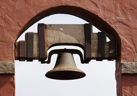 Old Spanish style bell hanging in a red brick wall