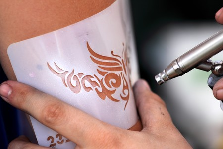 creating an air brush tatoo on a youn gilrs arm photo