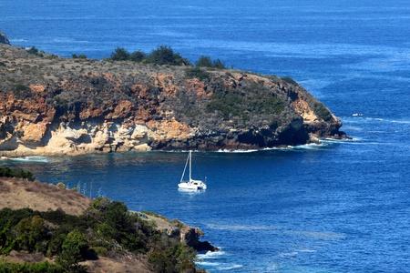 A sailboat in a bay at Santa Cruz Island with a blue ocean photo