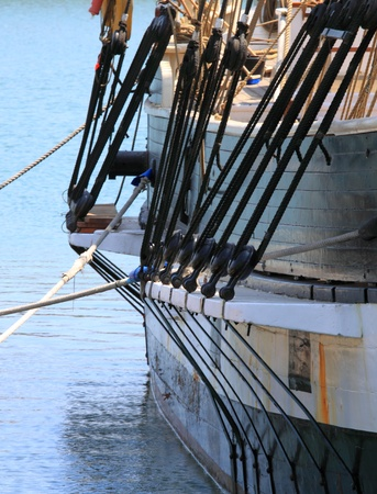 rigging of a sail boat with the blue water in the background photo