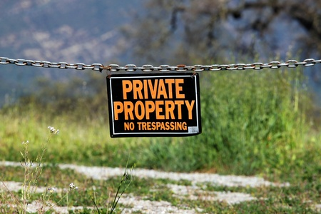 private information: black orange white private property hanging sign
