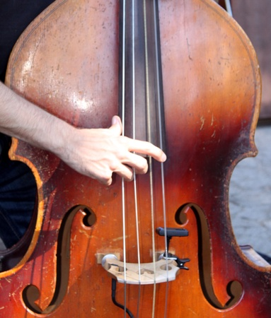 Hands playing a brown wooden bass Stock Photo