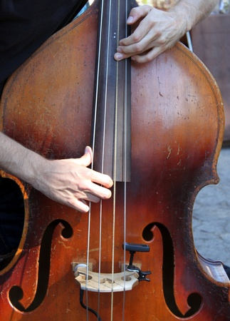 Hands playing a brown wooden bass photo