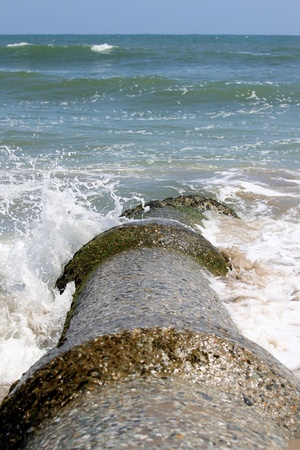 Sewage pipe having their outlet right into the ocean pollutiong the water. photo