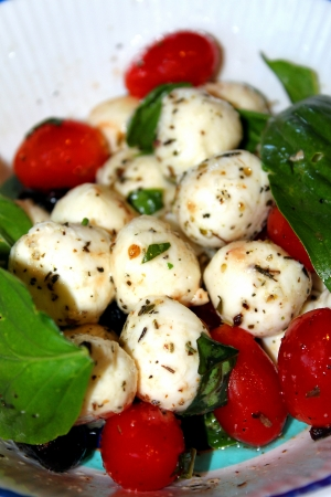 Closeup of a salad with mozarella balls with cherry tomatoes and basil