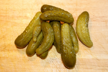 Green pickles on a borwn wooden chopping board Stock fotó