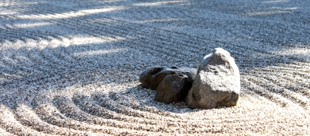 Zen stone garden wih a center rock and shadows Stock Photo