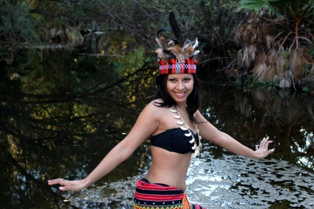 Native american woman dancing next to a creek. photo