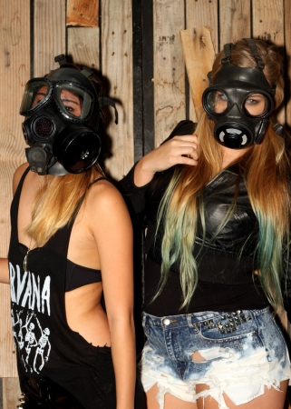 Two women in front of a wooden wall with gasmasks  photo