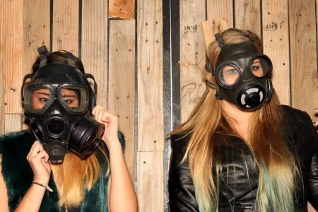 gasmask: Due donne di fronte a una parete in legno con maschere antigas
