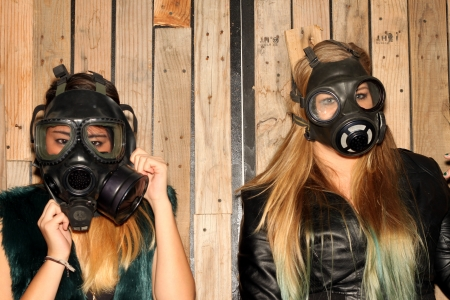 Two women in front of a wooden wall with gasmasks  Stock Photo
