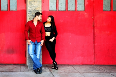 Young couple in front of red fire station doors
