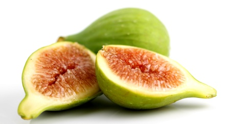 Green fig cut open on white background