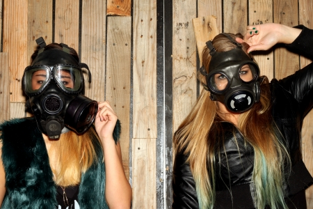 Two women in front of a wooden wall with gasmasks. photo