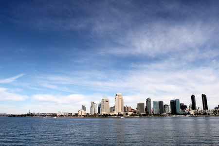 san diego: The skyline of San Diego with water in the front and cloudy blue sky in the background.