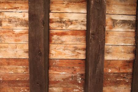 ceiling: Old brown wooden ceiling with dark beams.