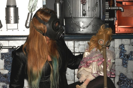 Woman with a gasmask and a puppet in front of a a wall. photo