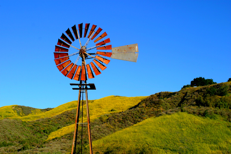 Water pumping windmill with a hill and blue sky in the background. photo