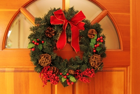 evergreen wreaths: Christams wreaths hanging on a wooden entrance door. Stock Photo