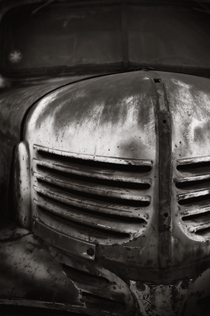 Image of an old rusty car in black and white.