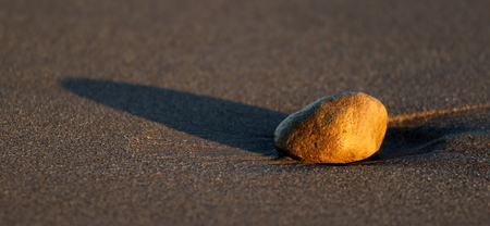 Stone at the beach in sand through sunset time.