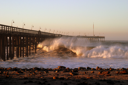 Ocean waves throughout at storm crashing into the wooden Ventura pier.