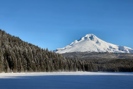 Mount Hood, Oregon in winter with a frozen Trillium Lake in the foreground, the frozen lake partly shaded in the early morning.