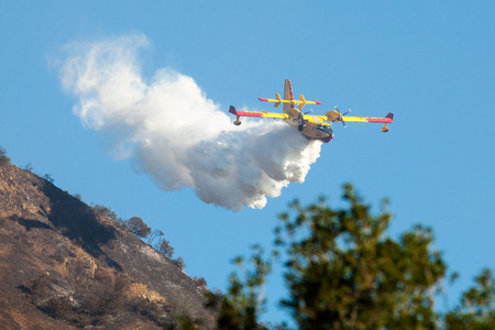 SAN DIMAS, CA - SEPT 10, 2014: Bombardier CL-415 Superscooper 246 from Quebec makes a water drop on a wildfire in the San Gabriel Mountains near Los Angeles.