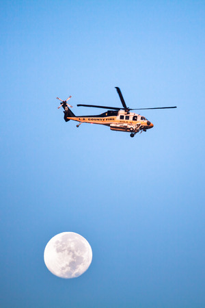 gabriel: SAN DIMAS, CA - SEPT 10, 2014: A Los Angeles County Fire helicopter makes a pass before proceeding to make a water drop on a wildfire in the San Gabriel Mountains.