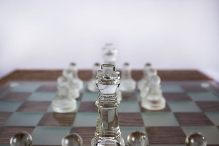 battle cross: Two units of glass chess pieces on the board are opposite to each other focus on white king