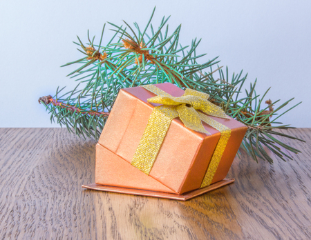 branche sapin noel: Red shiny gift box with gold bow and Christmas tree branch on the table
