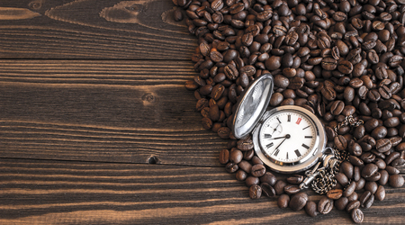 habbit: Old pocket watch lying on the coffee beans scattered on the old wooden table. Focus on dial