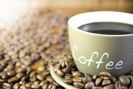 filiżanka kawy: Filiżanka kawy z ziaren stojąc na drewnianym stole. Crop, niewyraźne, koncentrują się na kubek