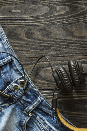 tracklist: The old faded jeans and headphones are in the corner of a wooden background. Top view