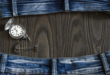 worn jeans: Frame made of old worn jeans and a pocket watch around a wooden background. Top view Stock Photo