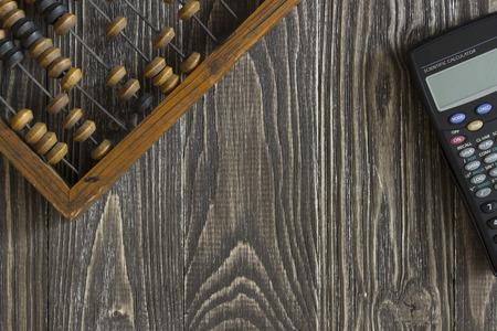 simbolos matematicos: �baco y calculadora acostado en una mesa de madera. Antecedentes vista desde arriba