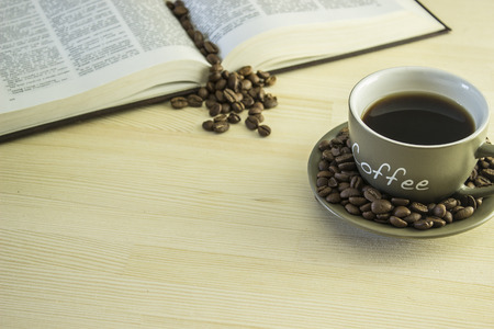 coffee mugs: The book and cup of coffee with beans on the wooden table