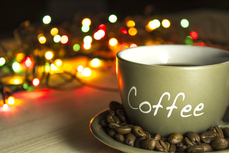 coffee mugs: Cup of coffee on a wooden table on a background of lights of a Christmas New Year garland
