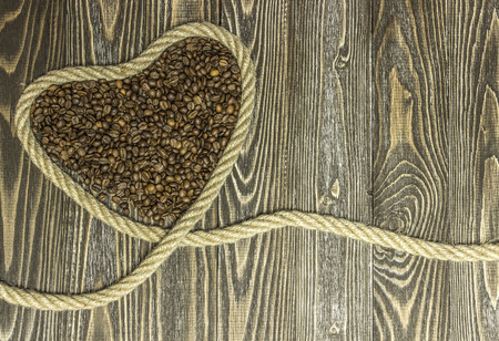 fourteenth: Heart shape made from coffee beans. Background for greeting cards for the holiday Valentines Day. Stock Photo