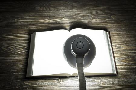 cognicion: El libro está iluminada por la luz de una lámpara sobre una mesa en una habitación oscura. Centrarse en la lámpara. Vista trasera Foto de archivo