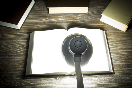 cognicion: The book is illuminated by light from a lamp on a table in a dark room. Focus on lamp. Back view