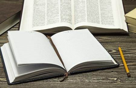 cognicion: Cuaderno y l�piz en el fondo de libros Foto de archivo