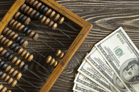 cash money: Old wooden abacus and a few dollar bills lying on a wooden table. Top View
