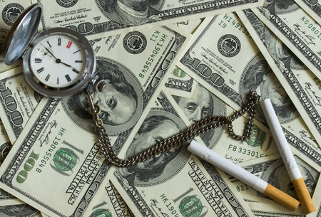habbit: Background texture of banknotes in denominations of one hundred dollars scattered on a table and an old pocket watch with two cigarettes