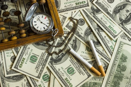 habbit: Background texture of banknotes in denominations of one hundred dollars scattered on a table and an old pocket watch with two cigarettes and old wooden abacus