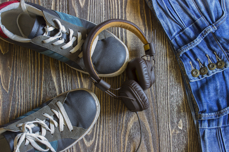 tracklist: Blue shoes vintage headphones and denim pants lie on wooden boards. Top view