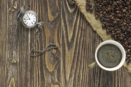 corner clock: A pocket watch with a cup of coffee and crema is in the corner of a wooden table on a burlap canvas close to crumble coffee beans. Close up. Top view