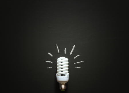 lay down: White shut down lamp with light painted with chalk lying on chalk board. Top view. Flat lay. Stock Photo