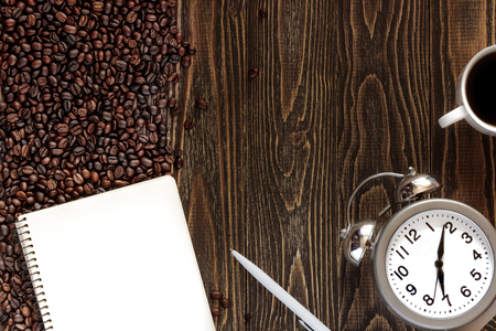 silver bells: single simple empty white notebook with a blank for drawing or writing, white plastic pen, scattered roasted coffee beans and alarm clock with silver bells are on a Desktop from wooden plank. Top view. Mock up. Flat lay