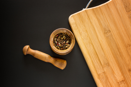 Food background. Wooden mortar with various spices and empty cutting board with blank space for mock up on black chalkboard. Topview. Mockup. Flatlay. Stock Photo